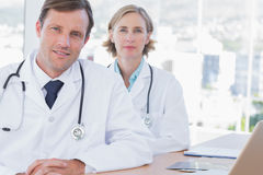 Group of doctors posing at their desk Royalty Free Stock Photography