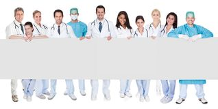 Group of doctors presenting empty banner. Isolated on white Royalty Free Stock Photos