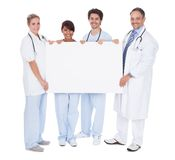 Group of doctors presenting empty board Stock Image