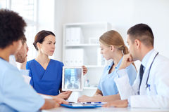Group of doctors with x-ray on tablet pc at clinic. Profession, people, surgery, radiology and medicine concept - group of doctors with x-ray on tablet pc Royalty Free Stock Photos