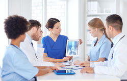 Group of doctors with x-ray on tablet pc at clinic. Profession, people, surgery, radiology and medicine concept - group of doctors with x-ray on tablet pc Stock Photos