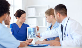 Group of doctors with x-ray on tablet pc at clinic. Profession, people, surgery, radiology and medicine concept - group of doctors with x-ray on tablet pc Stock Photography