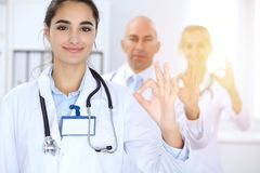 Group of doctors showing OK or approval sign with thumb up. High level and quality medical service, best treatment and. Patient care concept royalty free stock photo