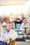 Group of doctors sits in break on stairs in clinic royalty free stock images