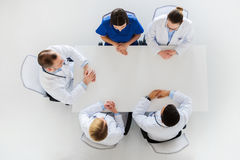 Group of doctors sitting at empty table Stock Photos