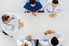 Group of doctors sitting at empty table Stock Image
