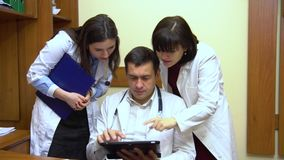 A group of doctors talking. Two women and a man. Male doctor keep a tablet. Close-up stock video footage