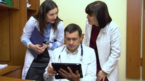 A group of doctors talking. Two women and a man. Male doctor keep a tablet. Close-up stock footage