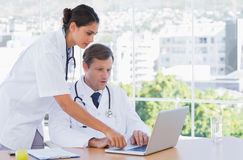 Group of doctors working together on a laptop. In a modern office Royalty Free Stock Image