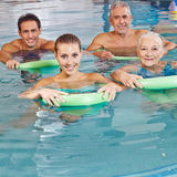 Group doing aqua fitness. Happy group doing together aqua fitness in swimming pool with swim noodles Royalty Free Stock Photo