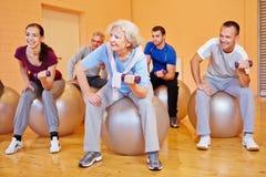 Group doing back training exercises. Happy group doing back training exercises in gym with dumbbells Stock Images