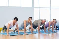 Group doing push ups in row at yoga class Stock Photos