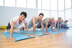 Group doing push ups in row at yoga class Stock Photography