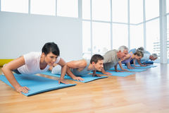 Group doing push ups in row at yoga class Stock Photo