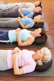 Group doing relaxation exercise. Group of seniors doing relaxation exercise in gym stock photos