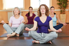 Group doing relaxing yoga exercises. Group of women doing relaxing yoga exercises in gym Royalty Free Stock Photo