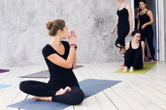 Group doing yoga at the gym. Welcoming on yoga class. Exercises starts indoors Stock Photo