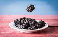 Group of dried plums. Ion the white plate on the wooden table royalty free stock image