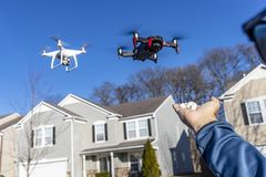 A Group Of Multiple Drones Fly Together Through The Air Against A Blue Sky Waiting To Be Fed. A group of drones fly through the air against a blue sky with a royalty free stock image