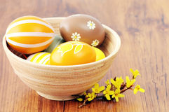 Group of easter eggs in a cup with Forsythia twig Royalty Free Stock Photo