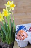 Group of Easter eggs with various waxy paintings, small holes and pictures in paper egg box. Wooden background, close up view, orange and blue color, yellow Royalty Free Stock Photos