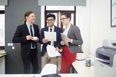 Friendly financiers. Group of economists reading and discussing papers and contracts royalty free stock image