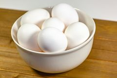 A group of eggs inside a deep white bowl next to a whisk waiting for the chef to use them in a meal royalty free stock photo
