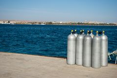 Group eight cylinders with air. eight aluminum cylinders on sea dock. Blue ocean and white steel cylinders royalty free stock images