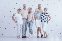 Elderly childhood friends. Group of elderly childhood friends posing for a photo together, meeting again after many years Royalty Free Stock Photo