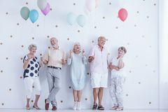 Family members laughing together. Group of elderly family members laughing together at a birthday party with colorful balloons Royalty Free Stock Photos