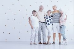 Group of elderly friends hugging each other in white studio with. Gold dots stock photo