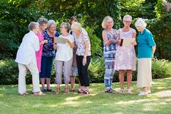 Group of elderly ladies at a care home enjoying a stimulating creative art class outdoors in a garden or park. Group of elderly ladies at a care home enjoying a royalty free stock images