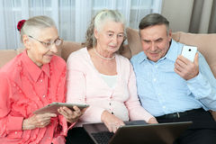 Group of elderly people. Group of older people having fun in communicating with the family on the internet in the comfortable livi Royalty Free Stock Photography