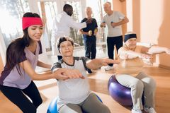A group of elderly women and men doing therapeutic gymnastics in a nursing home. A group of elderly women and men doing therapeutic gymnastics. A young Royalty Free Stock Photos