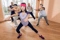 A group of elderly women and men doing therapeutic gymnastics in a nursing home. A group of elderly women and men doing therapeutic gymnastics. A young Stock Image