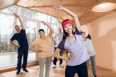 A group of elderly women and men doing therapeutic gymnastics in a nursing home. A group of elderly women and men doing therapeutic gymnastics. A young Royalty Free Stock Image