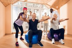 A group of elderly women and men doing therapeutic gymnastics in a nursing home. Royalty Free Stock Photo
