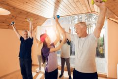 A group of elderly women and men doing therapeutic gymnastics in a nursing home. A group of elderly women and men doing therapeutic gymnastics. A young Stock Photo