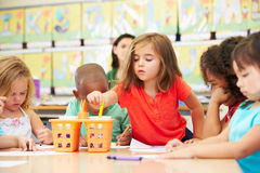 Group Of Elementary Age Children In Art Class With Teacher. Reaching For Crayon Royalty Free Stock Photo