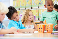 Group Of Elementary Age Children In Art Class With Teacher. Sitting Down Using Crayons Royalty Free Stock Images
