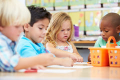 Group Of Elementary Age Children In Art Class. Using Coloured Crayons stock photography