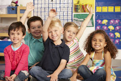 Group Of Elementary Age Schoolchildren Answering Question In Cla Stock Photo