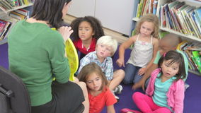 Group Of Elementary Age Schoolchildren Learning To Tell Time. Teacher sitting in chair explaining to a group of children how to tell the time using a model clock stock video footage