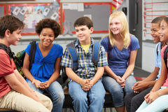 Group of Elementary Pupils In Classroom. Sitting on desks with backpacks on Stock Image