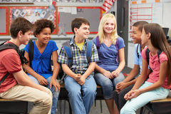 Group of Elementary Pupils In Classroom. Sitting on desks with backpacks on smiling and laughing Royalty Free Stock Image