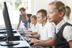 Group Of Elementary Pupils In Computer Class With Teacher Stock Photos