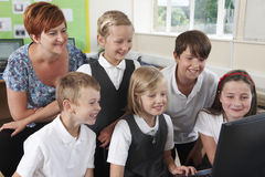 Group Of Elementary Pupils In Computer Class With Teacher Stock Images