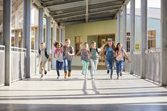 Group of elementary school kids running in a school corridor stock photography