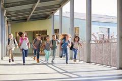 Group of elementary school kids running in a school corridor stock photo
