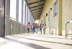 Group of elementary school kids running in a school corridor. Group of elementary school kid in a school corridor stock photo
